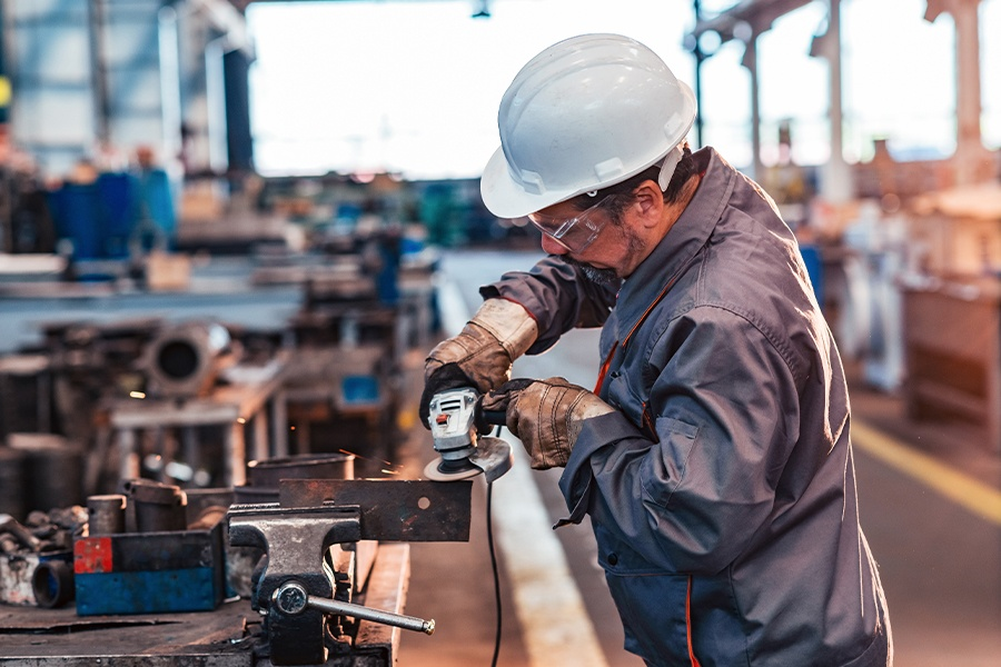 Specialized Business Insurance - Closeup of a Manufacturing Employee Working in a Metal Workshop